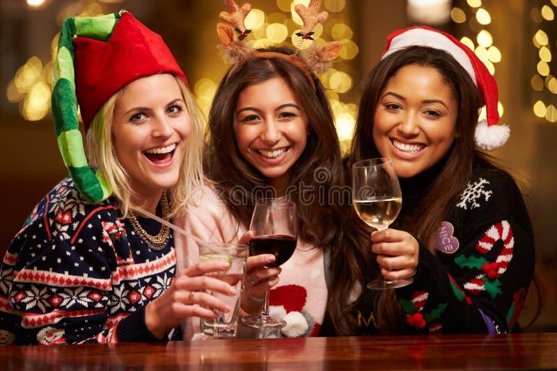 享受在酒吧的小组女性朋友圣诞节饮料 免版税库存照片
