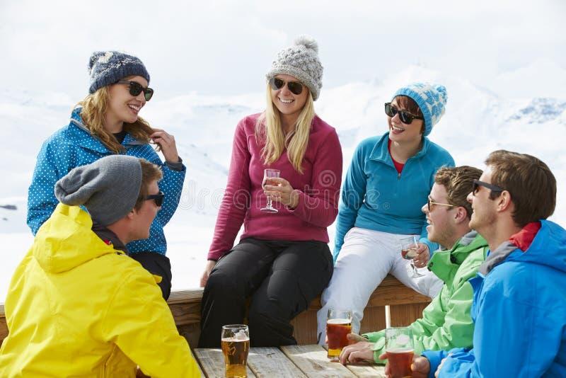 享受在酒吧的小组朋友饮料在滑雪胜地 免版税库存照片
