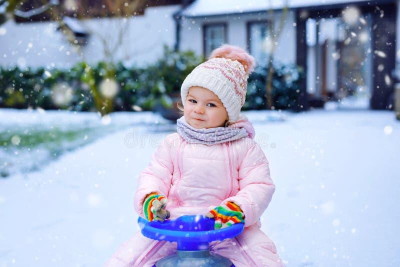 享受在雪的逗人喜爱的矮小的小孩女孩雪橇乘驾 儿童sledding 乘坐爬犁以五颜六色的时尚的婴孩孩子 免版税库存照片