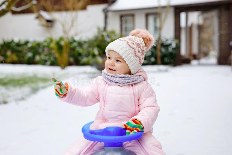 享受在雪的逗人喜爱的矮小的小孩女孩雪橇乘驾 ??sledding 乘坐爬犁以五颜六色的时尚的婴孩孩子 免版税库存图片