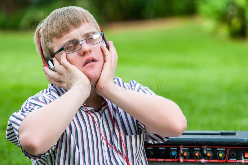 享受在顶头电话的有残障的男孩音乐 免版税库存照片