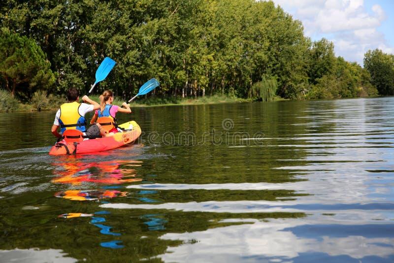 享受在晴天的夫妇独木舟乘驾 库存照片