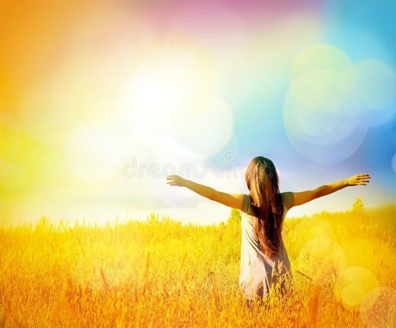 享受在晴朗的草甸的愉快的女孩幸福 免版税库存图片