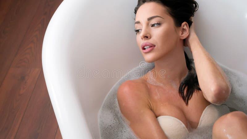 享受在浴缸的美丽的少妇时间 免版税库存照片
