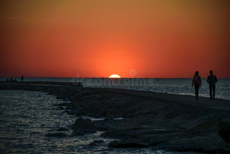 享受在brakewater的人们日落在海 免版税库存照片