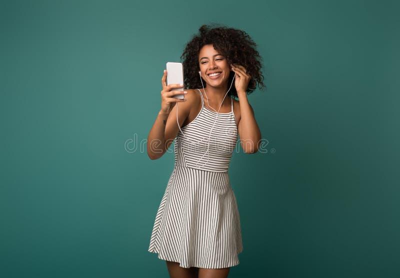 享受在earbuds的激动的妇女音乐在智能手机 免版税库存图片