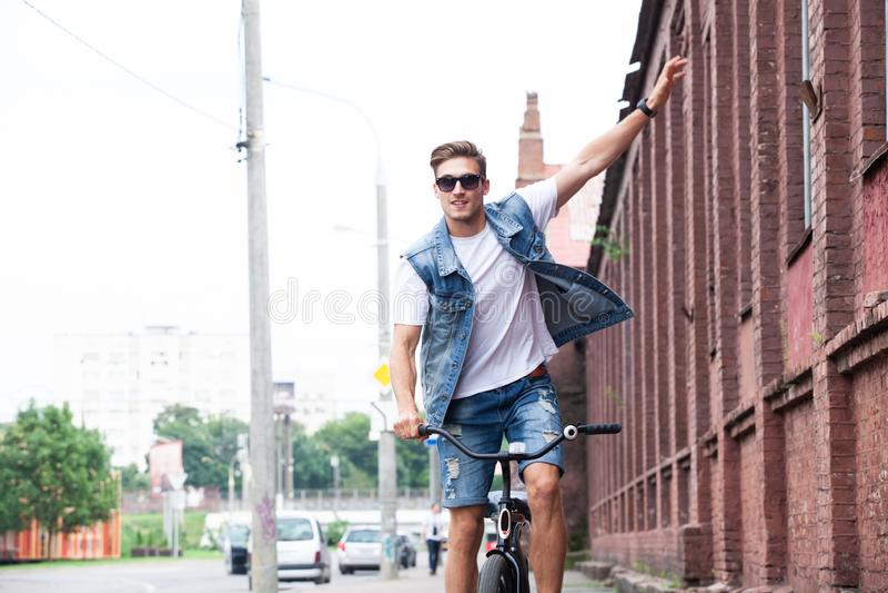 享受城市乘驾的英俊的行家乘自行车 库存图片