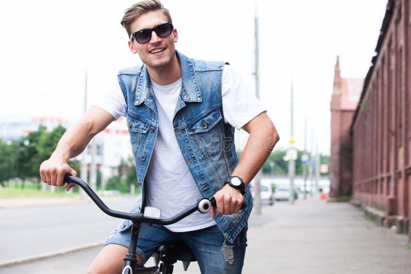 享受城市乘驾的英俊的行家乘自行车 免版税库存图片