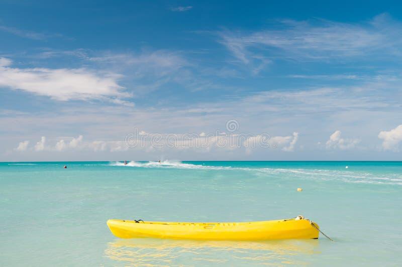享受夏天 花费假期扣人心弦的职业stjohns安提瓜岛 海绿松石水在海滩附近的黄色独木舟 极其 库存照片