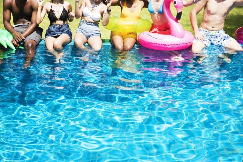 享受夏时的小组不同的朋友由与i的水池 库存照片