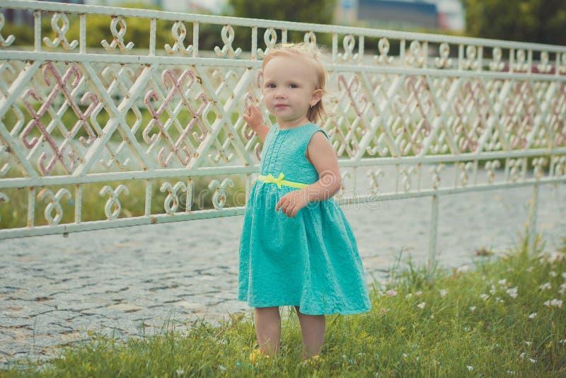 享受夏时的逗人喜爱的矮小的女婴在中央公园看见佩带的五颜六色的礼服和凉鞋与金发和桃红色ch 免版税库存图片
