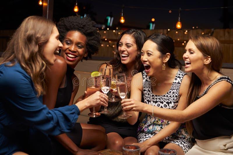 享受夜的小组女性朋友在屋顶酒吧 免版税库存图片