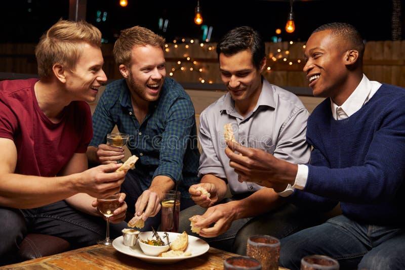 享受夜的小组男性朋友在屋顶酒吧 库存照片