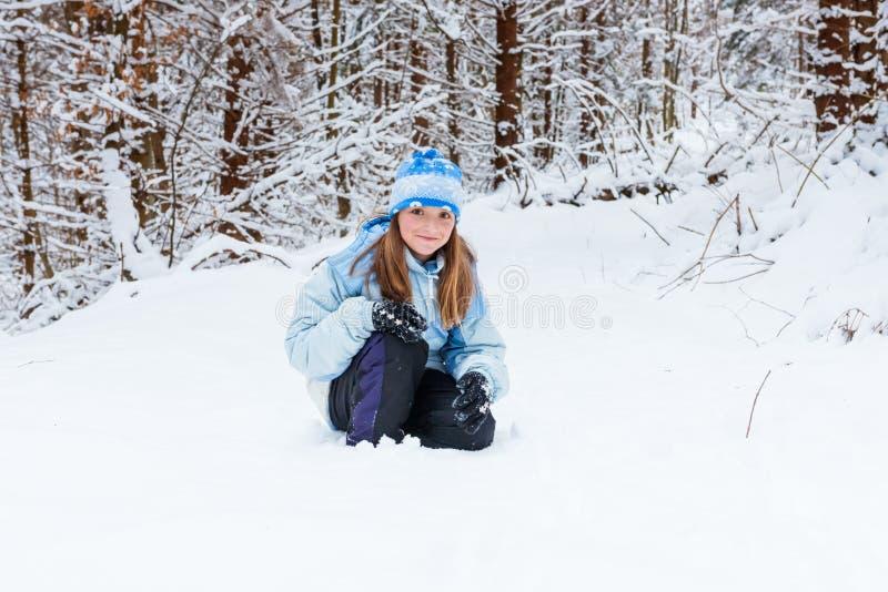 享受天的女孩使用在冬天森林里 免版税库存图片