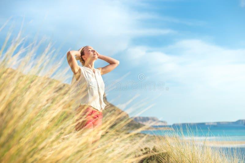 享受太阳的自由的愉快的妇女在度假 免版税图库摄影
