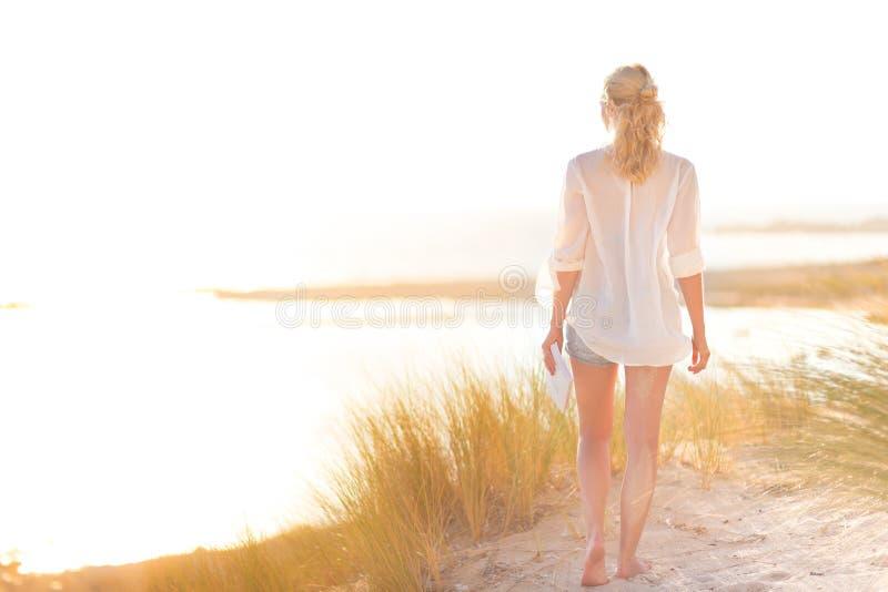 享受太阳的自由的愉快的妇女在度假 免版税库存照片