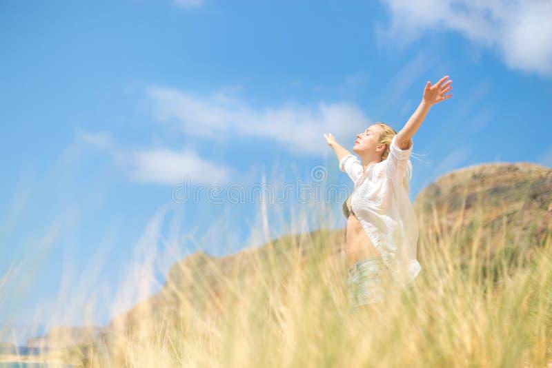 享受太阳的自由的愉快的妇女在度假 免版税库存图片