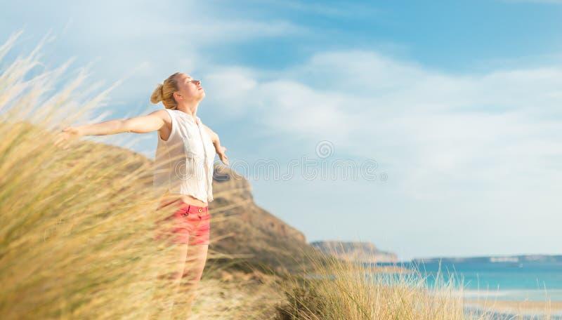 享受太阳的自由的愉快的妇女在度假 库存照片