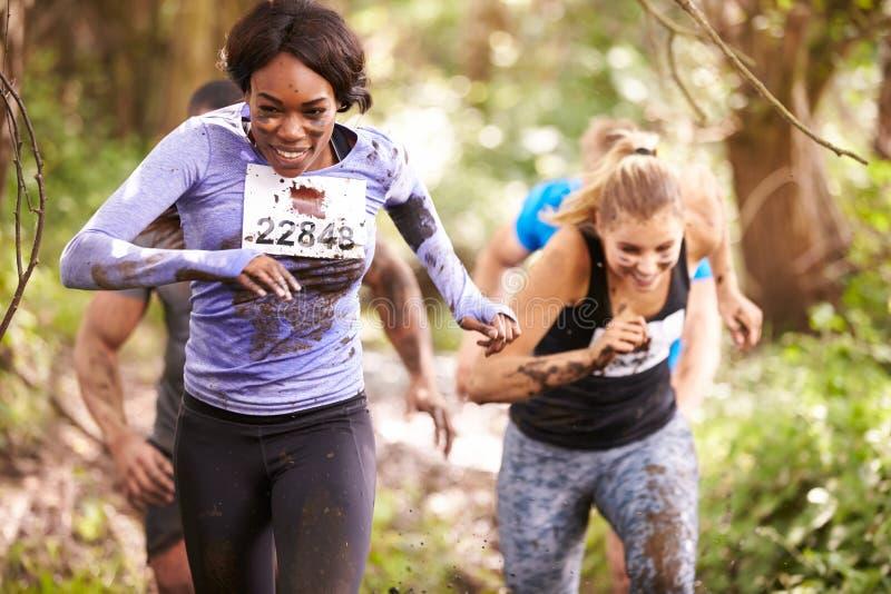 享受奔跑的两名妇女在森林里在耐力事件 免版税库存图片
