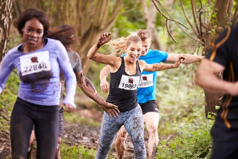 享受奔跑的竞争者在森林里在耐力事件 免版税库存照片