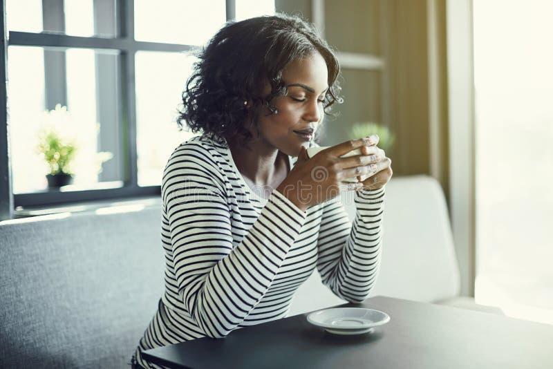 享受她新鲜的咖啡的芳香微笑的非洲妇女 免版税库存图片