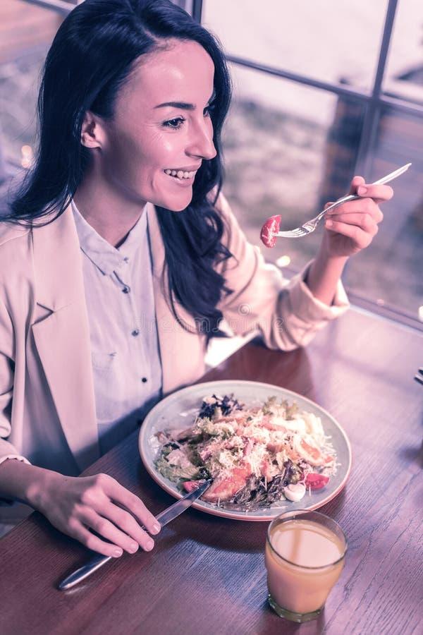 享受她的午餐的高兴正面好妇女 图库摄影