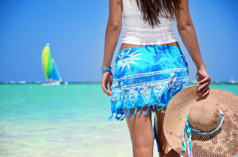 享受她的在异乎寻常的海滩的美丽的女孩暑假 库存图片