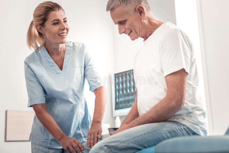 享受她的工作责任的微笑的金发的按摩医生 图库摄影