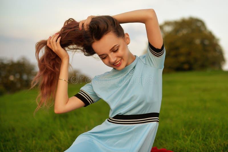 享受她的时间的可爱的少妇外面在日落公园 有壮观长头发摆在的式样女孩室外 秀丽, fa 免版税图库摄影