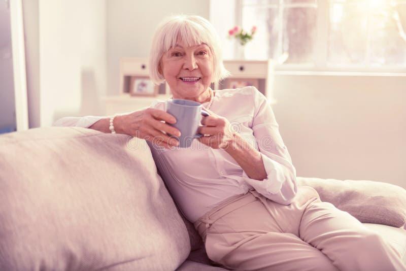 享受她的时间的灰发的年长妇女 免版税图库摄影