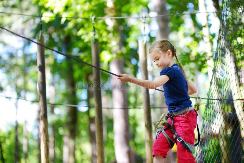 享受她的时间的可爱的小女孩在上升的冒险公园 免版税库存照片