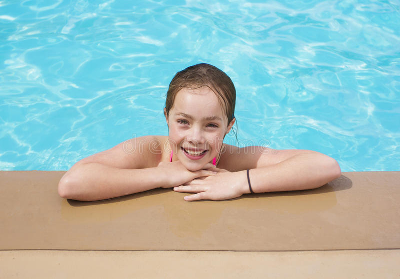 享受她的暑假的女孩在水池 免版税库存图片