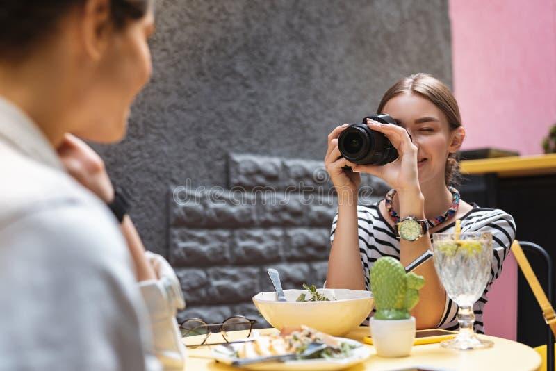享受她的职业的摄影师,当做照片朋友时 库存图片