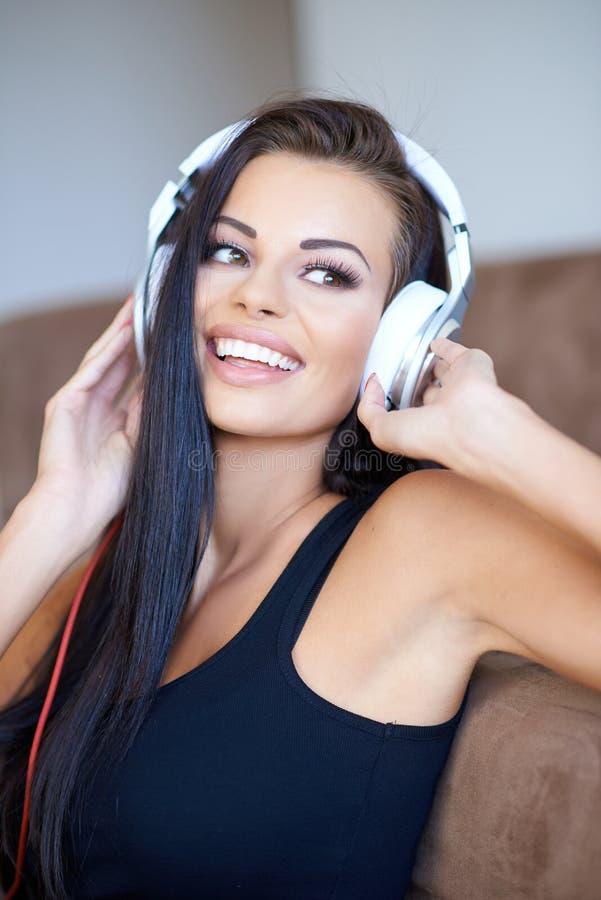 享受她的音乐的愉快的被晒黑的少妇 免版税库存照片