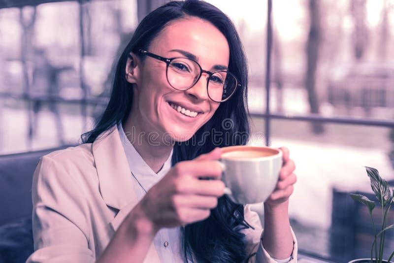 享受她的饮料的快乐的正面好妇女 免版税库存图片