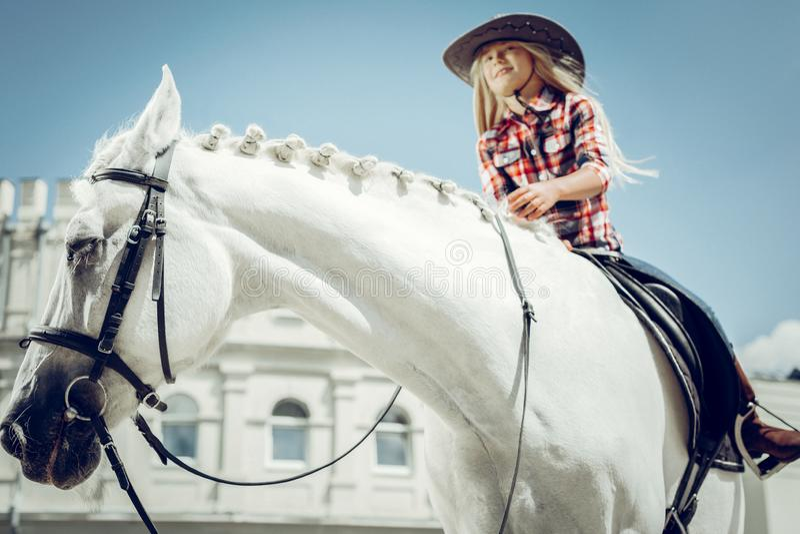 享受她的骑马课的好逗人喜爱的女孩 免版税图库摄影