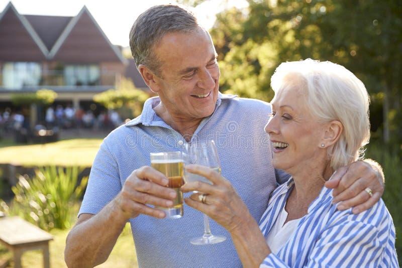 享受室外夏天饮料的资深夫妇在客栈 库存图片