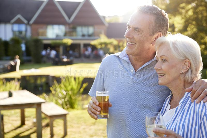 享受室外夏天饮料的资深夫妇在客栈 库存照片