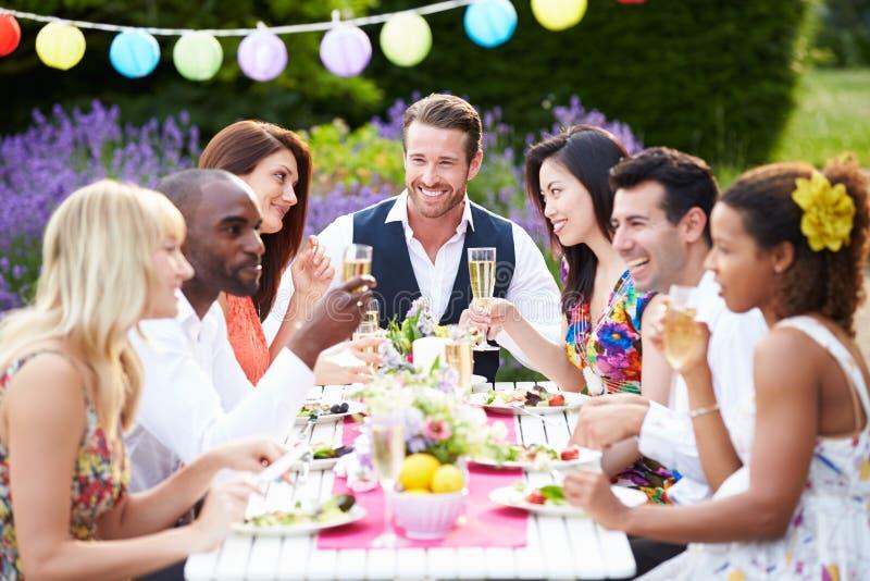 享受室外晚餐会的小组朋友 库存图片
