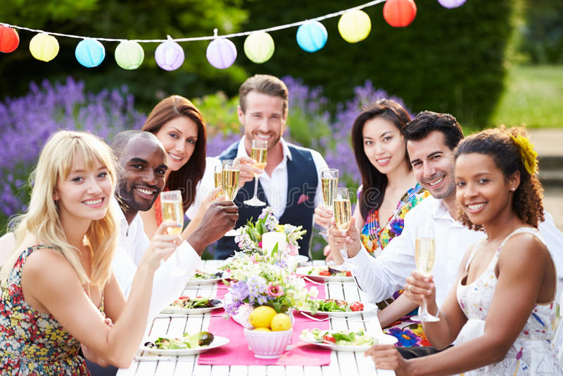 享受室外晚餐会的小组朋友 库存照片