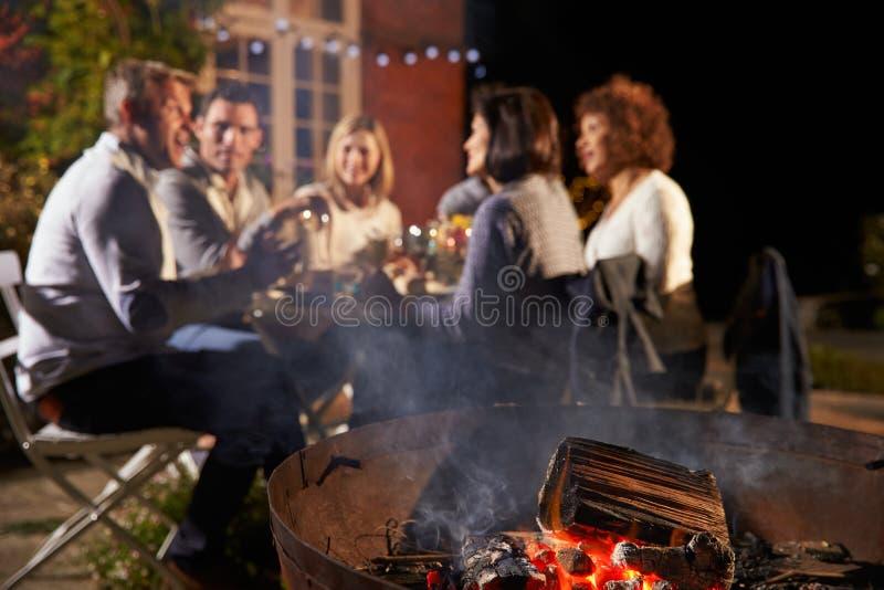 享受室外晚餐的成熟朋友在Firepit附近 免版税库存图片