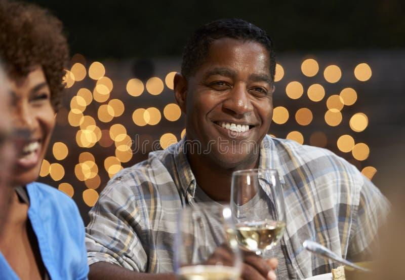 享受室外膳食的小组成熟朋友在后院 免版税库存图片