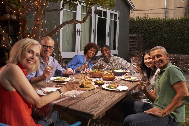 享受室外膳食的成熟朋友画象在后院 库存图片