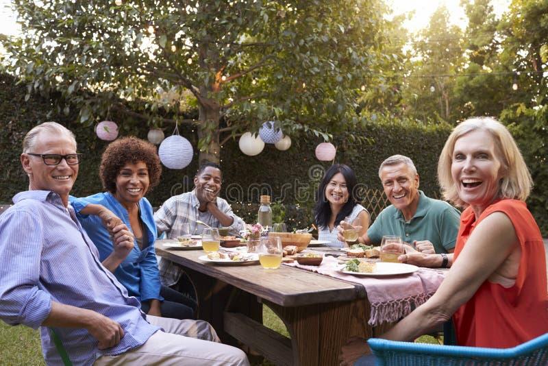 享受室外膳食的成熟朋友画象在后院 免版税库存照片