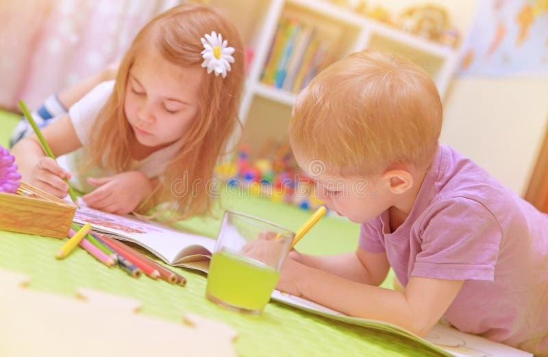 享受家庭作业的愉快的男婴&女孩 免版税库存照片
