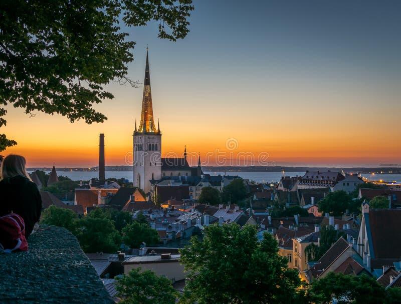 享受屋顶上面和教会尖顶的看法的人 库存图片