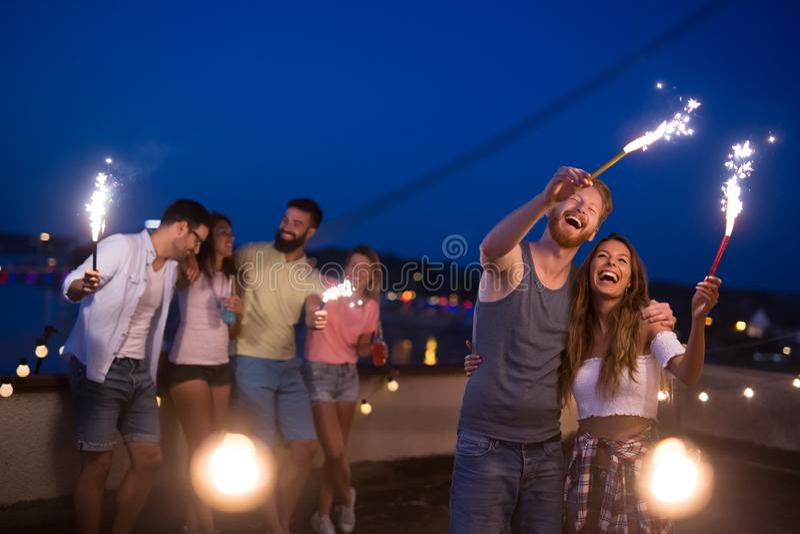 享受屋顶党和跳舞与闪烁发光物的朋友 免版税图库摄影
