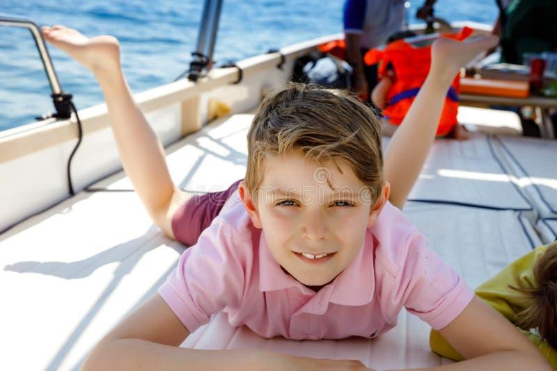 享受帆船旅行的愉快的白肤金发的孩子男孩 在海洋或海的家庭度假在好日子 健康美丽的学校 库存照片