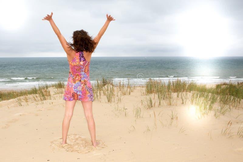 享受平静的海洋自然的微笑自由和幸福旅游妇女 免版税库存照片