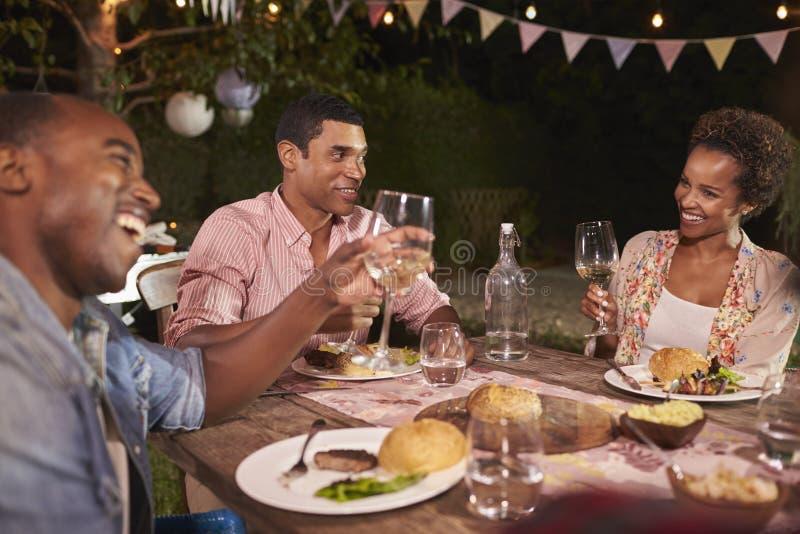 享受庭院晚餐会的三个年轻黑成人 免版税库存图片